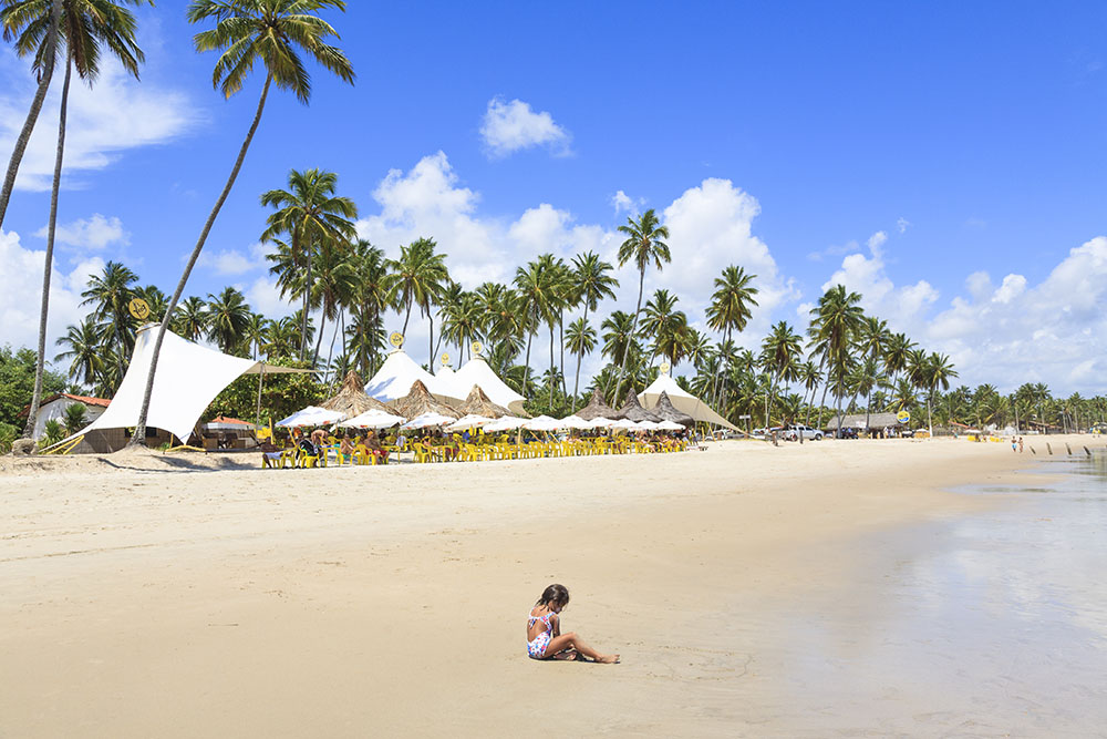 Das Hauptmotiv ist der palmengesäumte Strand und den vielen unterschiedlich großen Zelten der Strandbar. Durch das Kind im Vordergrund erhält das Bild eine räumliche Tiefe, die es insgesamt interessanter macht. Ohne das Kind würde es dem Bild eindeutig an Tiefe fehlen.