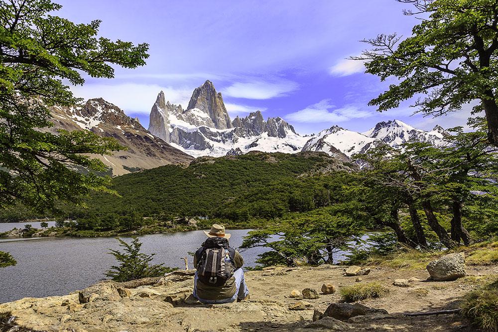 """Die Aufnahme vom Fitz Roy in Patagonien hat durch den Felsen und die Bäume einen Vordergrund. Die Bäume geben dem Bild zusätzlich einen Rahmen, die den Betrachter ins Bild """"hinein"""" schauen lassen. Die Person im Vordergrund verstärkt zusätzlich diesen Eindruck."""